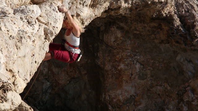 Young woman climbs over overhanging rock lip