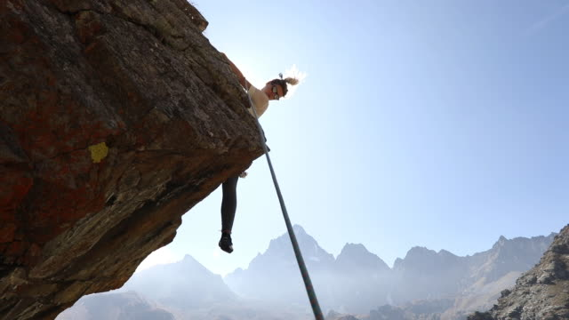 young woman climbs overhanging rock buttress - adversity stock videos & royalty-free footage