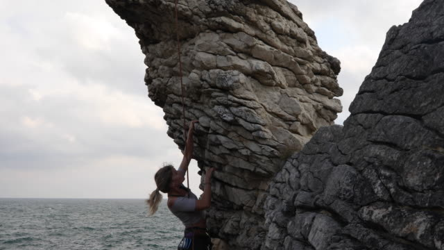 young woman climbs overhanging rock to man belaying - surf rock stock videos & royalty-free footage
