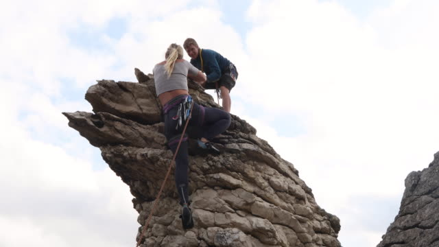 young woman climbs overhanging rock to man belaying - rock climbing stock videos & royalty-free footage