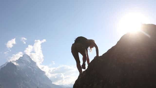 stockvideo's en b-roll-footage met young woman climbs rock ridge above mountains - bergrug