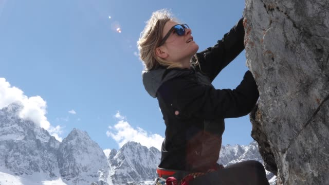 young woman climbs vertical rock buttress, with rope - sunglasses stock videos & royalty-free footage