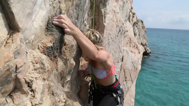 stockvideo's en b-roll-footage met young woman climbs vertical rock cliff above sea - rotsklimmen