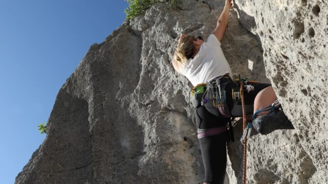 young woman climbs vertical rock face, while leading - millennial generation stock videos & royalty-free footage