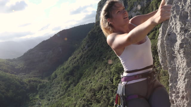 young woman climbs vertical rock wall, above forest - carrellata video stock e b–roll