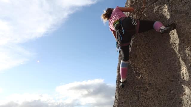 vídeos de stock, filmes e b-roll de jovem sobe parede de rocha vertical, em pequenos porões - paredão rochoso