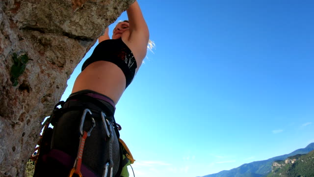 young woman climbs vertical rock wall - corda video stock e b–roll