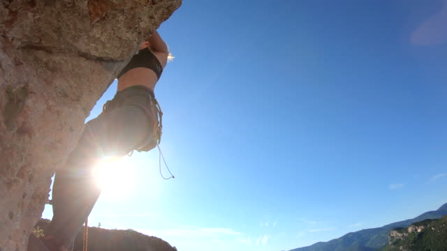 young woman climbs vertical rock wall - climbing stock videos & royalty-free footage