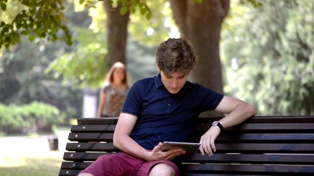 若い女性は彼女のボーイ フレンド彼はデジタル タブレットでネット サーフィンしながら眼を閉じる