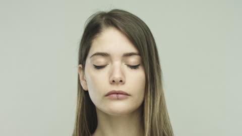 vídeos y material grabado en eventos de stock de mujer joven cerrando los ojos sobre fondo gris - ojos cerrados