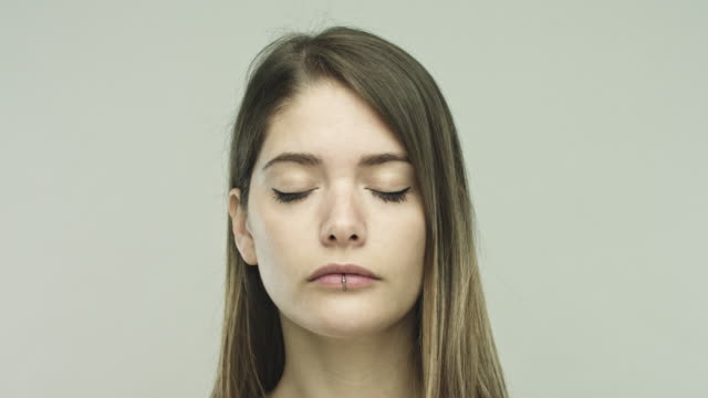 Young woman closing eyes on gray background