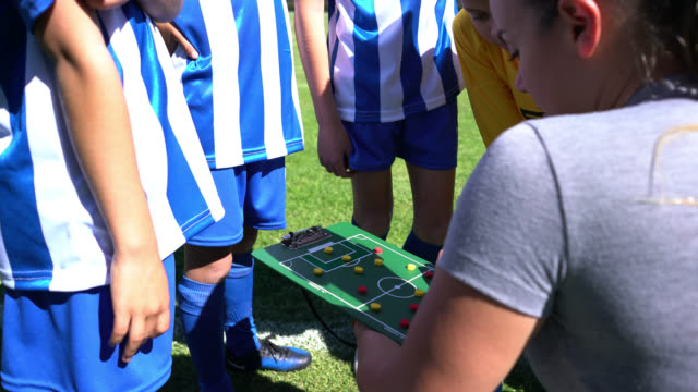 young woman coaching a group of kids in a soccer practice using a board to show them the line up - summer camp stock videos & royalty-free footage