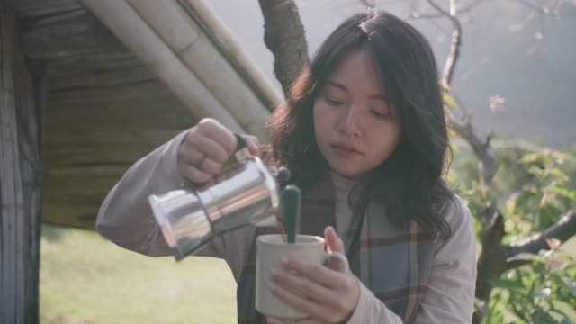 young woman coffee pouring into a cup at picnic table in the forest in the morning. - kitchenware shop stock videos & royalty-free footage