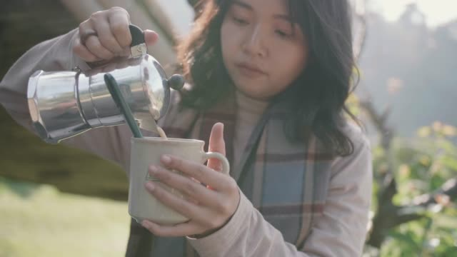 young woman coffee pouring into a cup at picnic table in the forest in the morning. - kitchenware department stock videos and b-roll footage