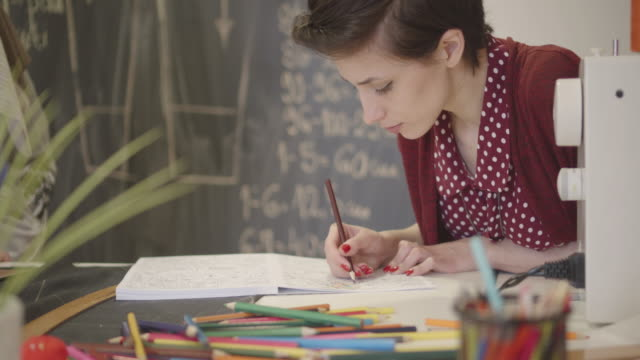 4K: Young Woman Coloring Book In Her Sewing Office.