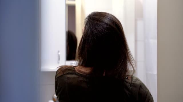 vídeos de stock, filmes e b-roll de mulher nova que penteia o cabelo - brown hair