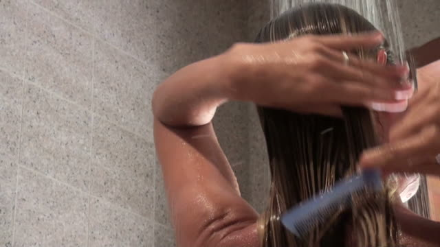 young woman combing hair while taking her shower - washing hair stock videos & royalty-free footage
