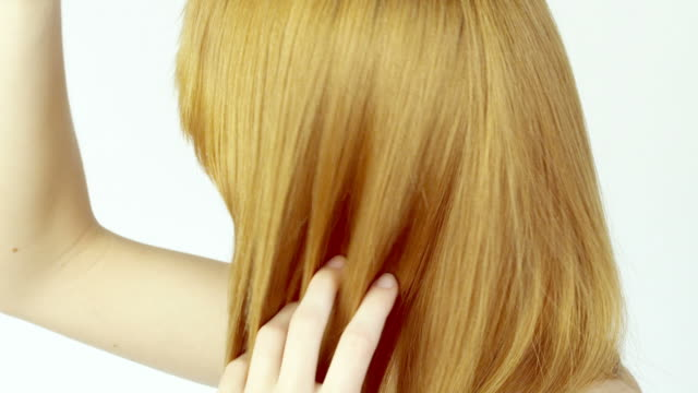 Young woman combing her hair.