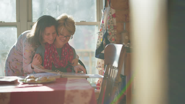 young woman comes up and hugs her mother while she's looking through holiday recipes - multi generation family stock videos & royalty-free footage