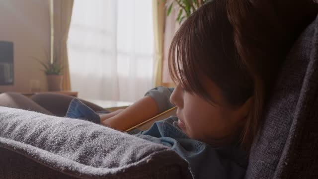 giovane donna che dorme comodamente sul divano mentre tiene il libro in soggiorno a casa - letteratura video stock e b–roll