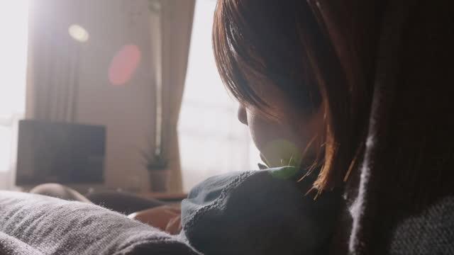 自宅のリビングルームで本を持ちながらソファで快適に寝る若い女性 - 怠惰点の映像素材/bロール