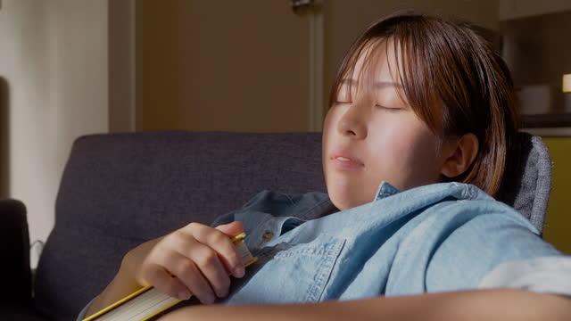自宅のリビングルームで本を持ちながらソファで快適に寝る若い女性 - resting点の映像素材/bロール