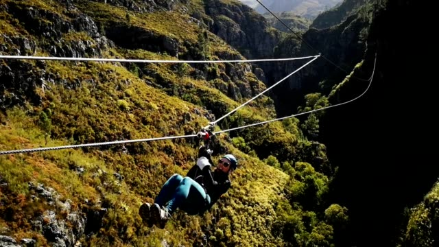 young woman coming down zip  line in south africa hd video - zip line stock videos & royalty-free footage