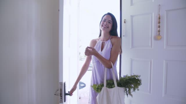 vídeos y material grabado en eventos de stock de ms young woman coming home from shopping - bolsa reutilizable