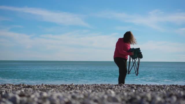 junge frau kommt ans meer und sitzt am strand, 4k video - dicke frauen am strand stock-videos und b-roll-filmmaterial