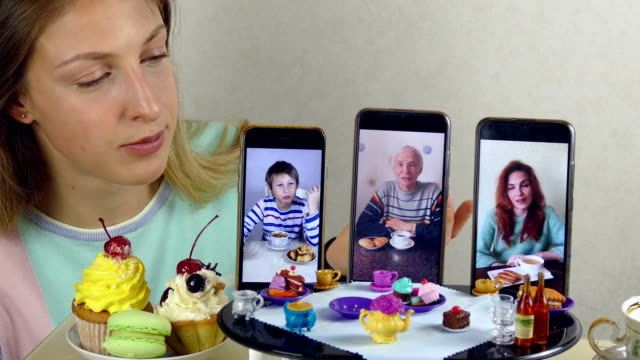young woman communicates with family while drinking tea at a toy table using video calling - puppet stock videos & royalty-free footage