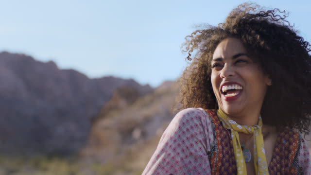 SLO MO. Young woman communing with nature laughs at camera and smiles at the sun in Nevada desert.
