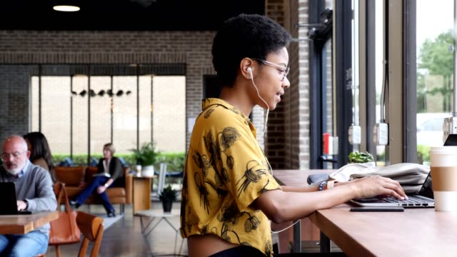 young woman concentrates while using laptop in coffee shop - young women stock videos & royalty-free footage
