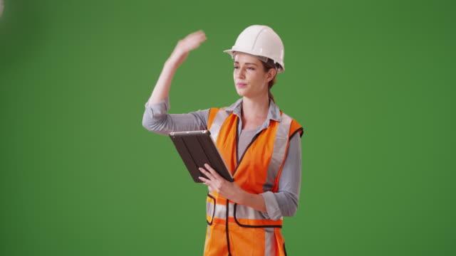vídeos y material grabado en eventos de stock de young woman construction manager directing traffic on green screen - cuello parte de la vestimenta