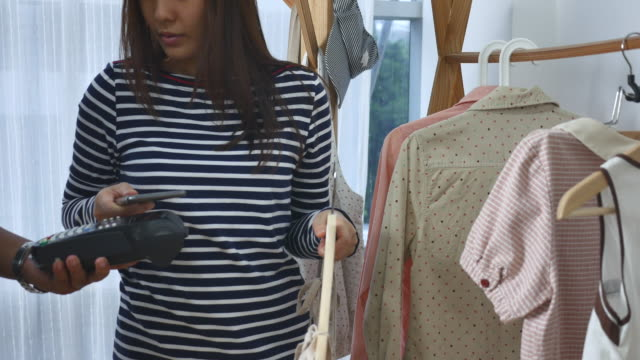Young woman Contactless Payment with Smart phone and clothes
