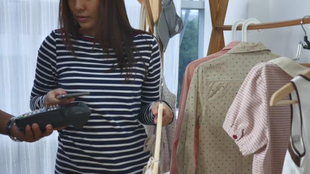 Junge Frau kontaktloses Bezahlen mit Smartphones und Kleidung
