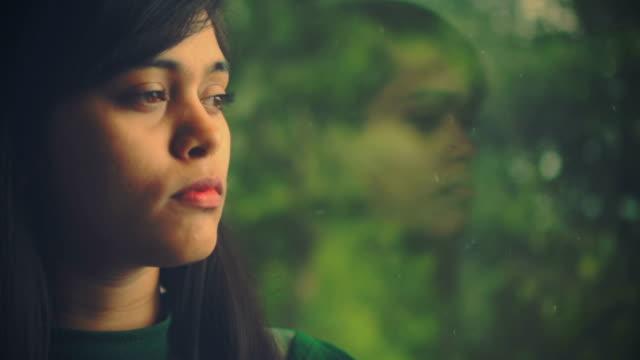 vídeos y material grabado en eventos de stock de la joven contempla y mira una vista a través de la ventana. - mirar hacia el otro lado