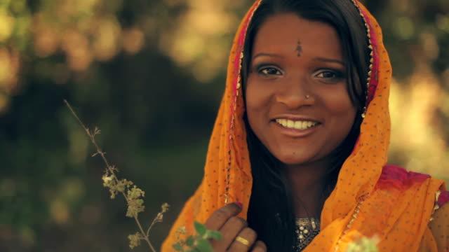 若い女性は、歯の笑顔でカメラを熟考し、見ます。 - 民族衣装点の映像素材/bロール