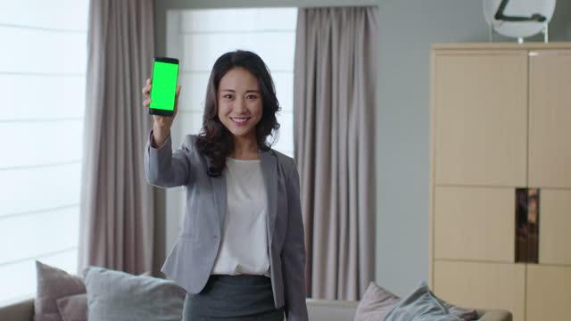 vídeos de stock, filmes e b-roll de young woman controlling home appliance by mobile app on smartphone,4k - exposição