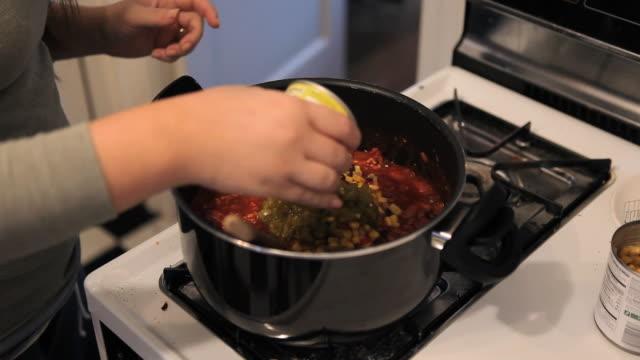 vídeos de stock, filmes e b-roll de ms young woman cooking chili / richmond, virginia, usa - fogão