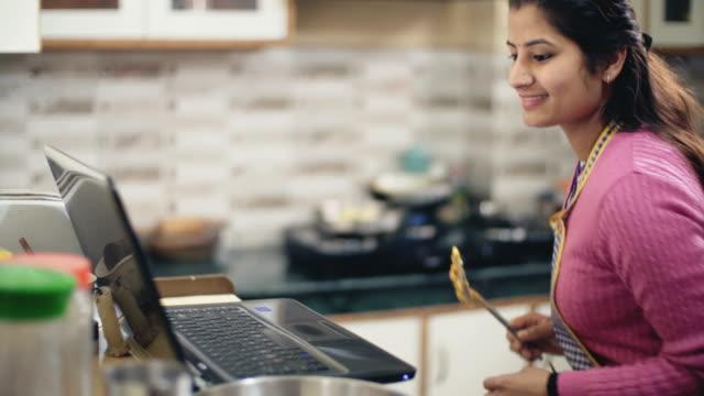 junge frau in der küche zu kochen. - etwas herstellen stock-videos und b-roll-filmmaterial