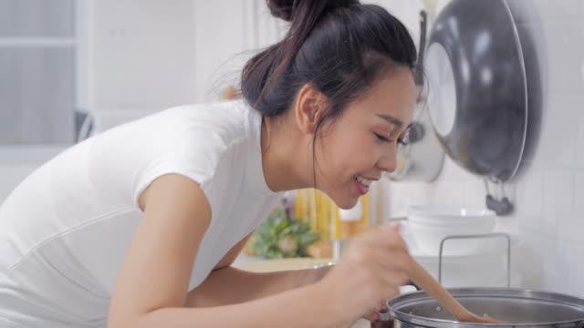 vidéos et rushes de jeune femme dans son statut de cuisine près de poêle de cuisson - sentir
