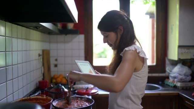 stockvideo's en b-roll-footage met jonge vrouw koken saus en het gebruik van digitale tablet in de keuken - koken toestand