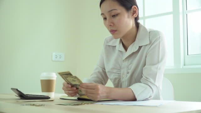 young woman counting cash managing personal finances in living room - only young women stock videos & royalty-free footage