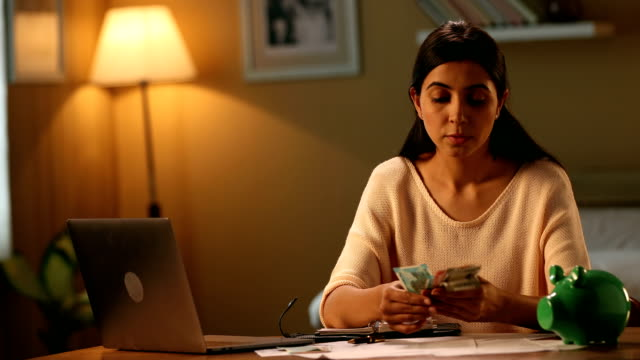 ms young woman counting her money and putting into piggy bank for savings / new delhi, delhi, india - wages stock videos & royalty-free footage