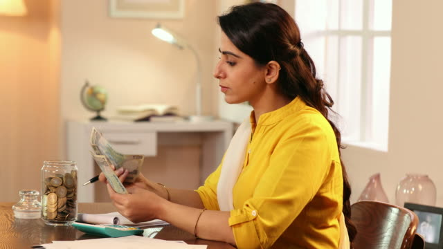 ms young woman counting money and writing on notepad in house / delhi, india - jar stock videos & royalty-free footage
