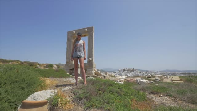 a young woman couple in front of ancient ruins of the apollo temple, traveling in naxos, greece, europe. - slow motion - naxos greek islands stock videos & royalty-free footage