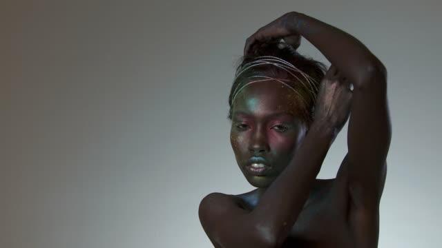 young woman covered in metallic makeup, moving and turning - människoarm bildbanksvideor och videomaterial från bakom kulisserna