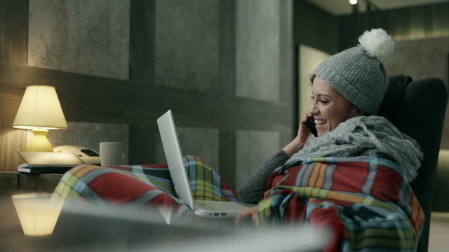 Young woman covered with a blanket using laptop and phone