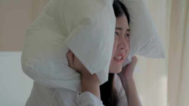 young woman covering ears with pillow while trying to sleep in bed,early morning - pillow stock videos & royalty-free footage