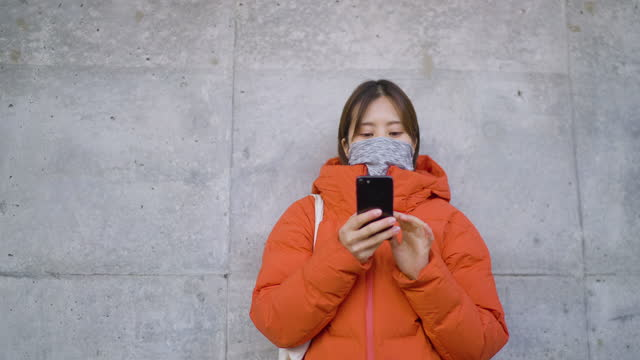 young woman covering her face with bandana face mask and using smart phone in front of concrete wall in winter - concrete wall stock videos & royalty-free footage